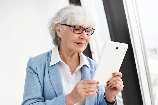 Pozostawanie w kontakcie. nowoczesna inteligentna starsza kobieta z siwymi włosami pozuje odizolowana w okularach i formalnym ubraniu, czytając książkę elektroniczną lub robiąc zakupy online za pomocą cyfrowego tabletu, mając zadowolony, szczęśliwy wygląd