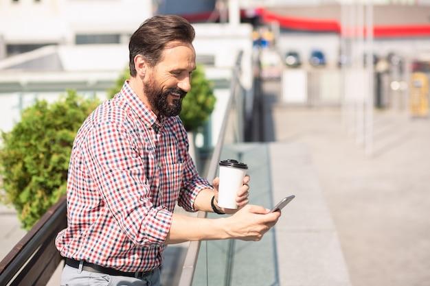 Pozostawanie w kontakcie. optymistyczny brodaty mężczyzna pije kawę podczas korzystania z telefonu