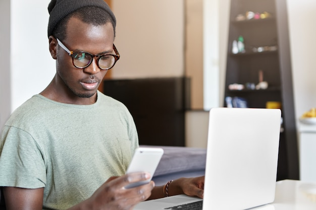 Pozostawanie w kontakcie. stylowy ciemnoskóry mężczyzna używa swojego smartfona do bankowości internetowej, płacąc za bezprzewodowy internet w domu podczas pracy na laptopie. ludzie, nowoczesna technologia i komunikacja