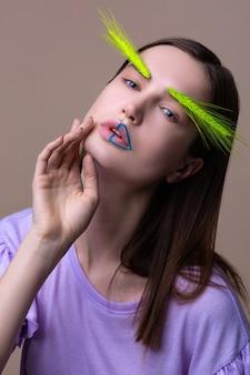 Pozowanie do okładki. model pozujący na okładkę magazynu ekologicznego z kolcem na brwiach i niebieskimi kreskami na ustach