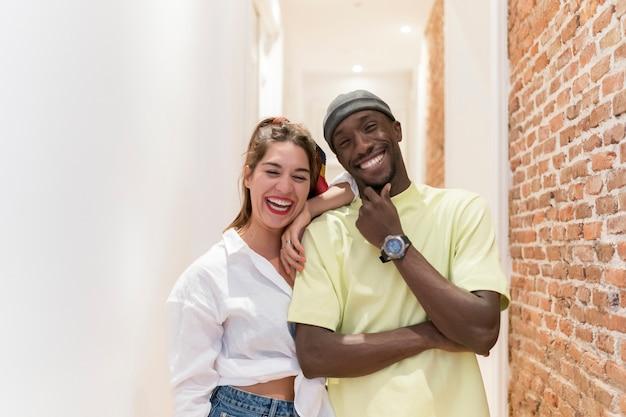 Pozowanie szczęśliwy międzyrasowy przyjaciół. mają na sobie jasne ubrania. ceglana ściana i biały korytarz