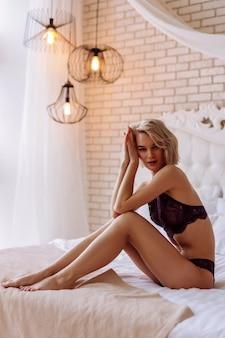 Pozowanie w bieliźnie. atrakcyjna piękna modelka czuje się zajęta podczas pozowania w seksownej koronkowej bieliźnie