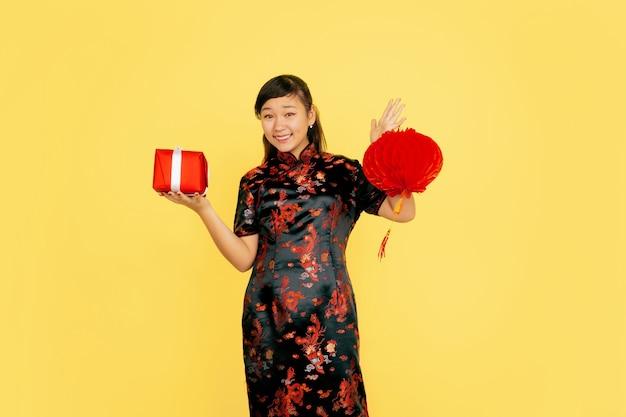 Pozowanie z latarnią i prezentem, uśmiechnięte. szczęśliwego chińskiego nowego roku 2020. portret azjatyckiej młodej dziewczyny na żółtym tle. modelka w tradycyjne stroje wygląda na szczęśliwą. świętowanie, emocje. copyspace.