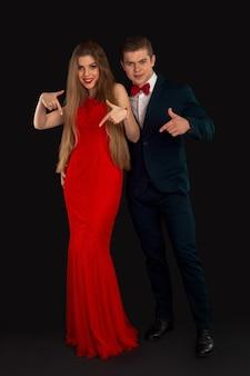 Pozują kobieta w czerwonej sukience i mężczyzna w stroju