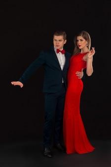 Pozują mężczyzna w stroju i kobieta w czerwonej sukience