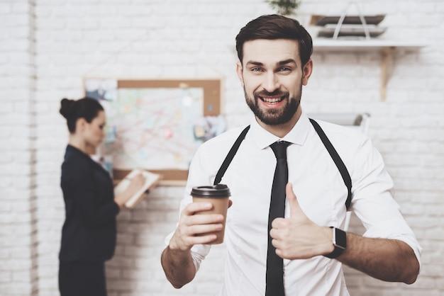 Pozuje z kawą, kobieta patrzy na mapę wskazówek.