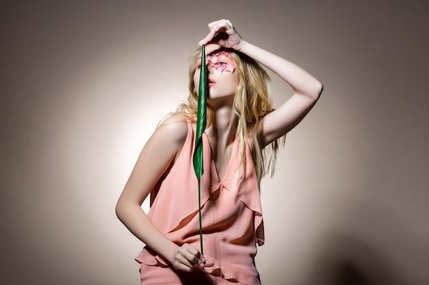 Pozuje z liściem. blondwłosa modelka w ładnej sukience pokazująca pozy, trzymająca w dłoniach liść
