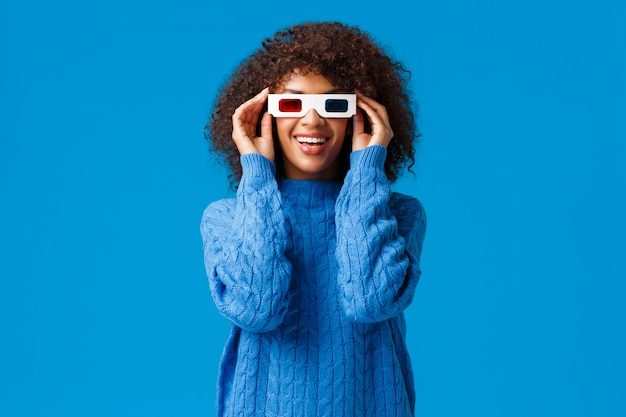 Pozwala oglądać i odpocząć. szczęśliwa charyzmatyczna afroamerykańska kobieta korzystająca z premiery nowego niesamowitego filmu, w okularach 3d idź do kina i uśmiechając się jak zafascynowany wyglądający ekran, stojąca niebieska ściana