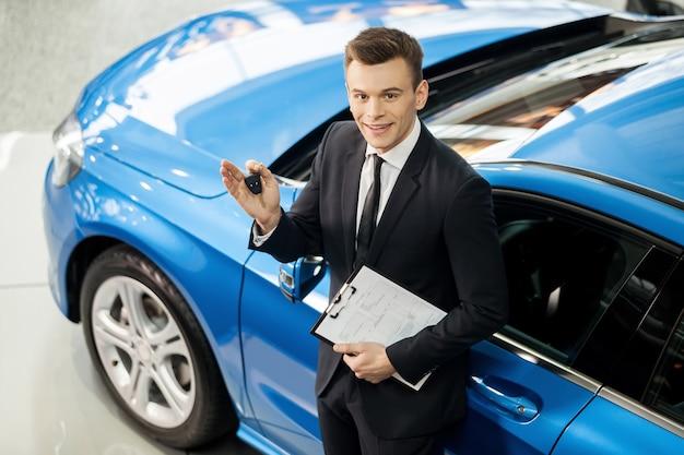 Pozwól, że pomogę ci w wyszukiwaniu pojazdu. widok z góry na przystojnego młodego sprzedawcę klasycznych samochodów stojącego w salonie, trzymającego klucz