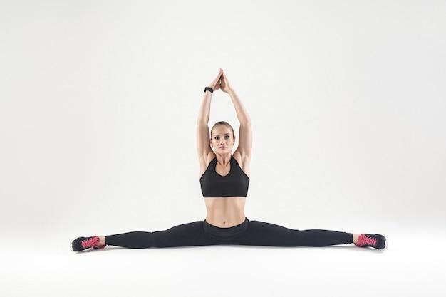 Pozycja gimnastyczna, rozciąganie. młoda dorosła blondynka, robi ćwiczenia krzyżowe. studio strzał, szare tło