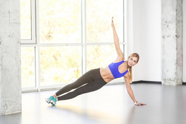 Pozycja jogi. ćwiczenie vasisthasany. blondynka równoważenia z jednej strony. zdjęcia studyjne