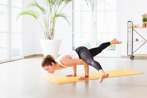 Pozycja jogi lub latające pęknięcia pozycji równowagi ramion wykonywanych przez kobietę