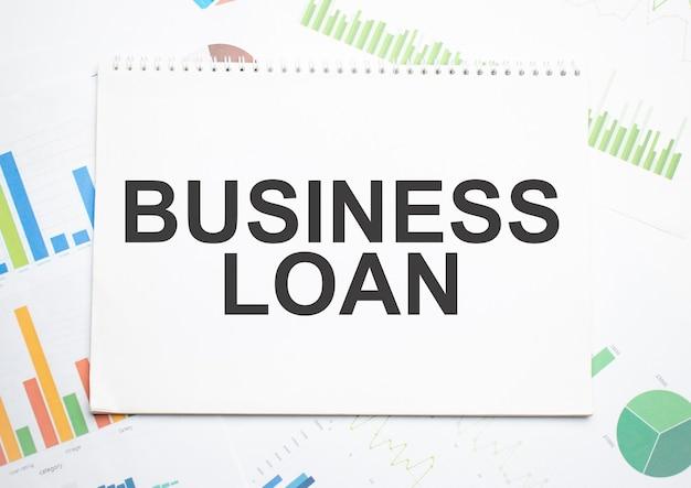 Pożyczka biznesowa, etykieta tekstowa w notatniku planowania oraz wykres statystyk. analiza rynku, skuteczna strategia biznesowa.