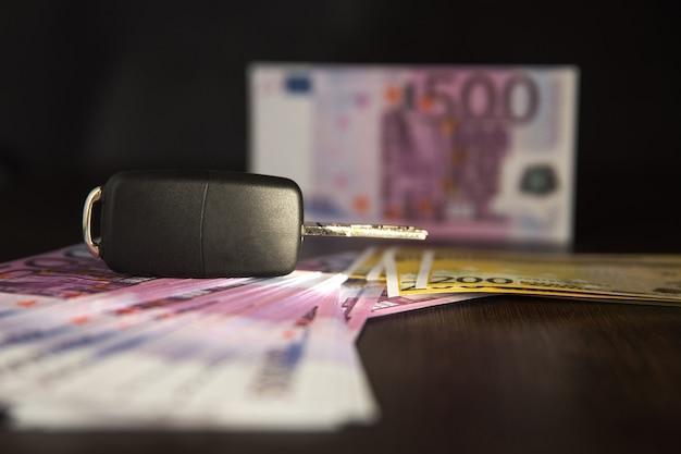 Pożyczka symulacyjna na zakup samochodu. gotówka na samochód - kluczyk do samochodu na tle banknotów euro. klucze z samochodu na banknotach euro.