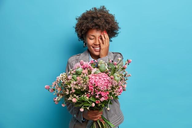Pozytywna afro amerykanka kobieta trzyma piękny bukiet kwiatów otrzymanych na urodziny obejmuje twarz ręką ubraną w szarą kurtkę na białym tle nad niebieską ścianą