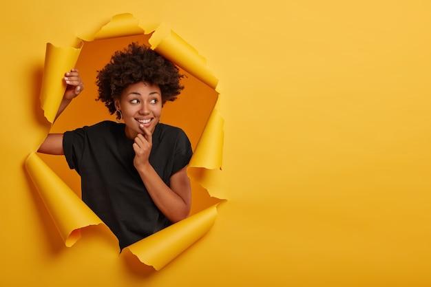Pozytywna afro dziewczyna trzyma podbródek, skupiona na boku, czuje się uroczo i wesoło, nosi casualową koszulkę, pozuje samotnie w papierowej dziurze
