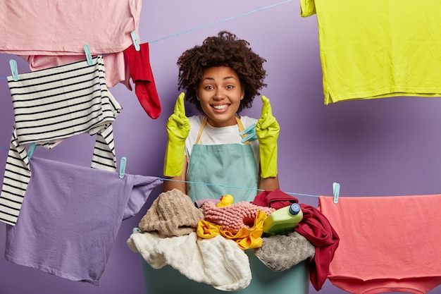 Pozytywna afro kobieta trzyma kciuki, liczy na szczęście, stoi za stosem ubrań, nosi fartuch, rękawiczki ochronne, w wolnych chwilach myje, chce skończyć prace domowe na czas. gospodarowanie