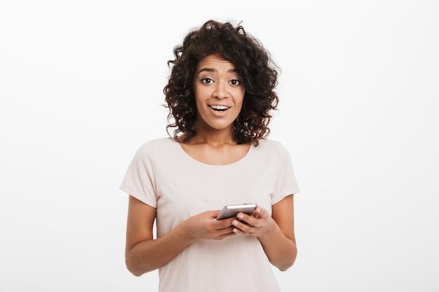 Pozytywna afroamerykanin kobieta z kręconymi włosami, trzymając telefon komórkowy i odizolowane na białej ścianie