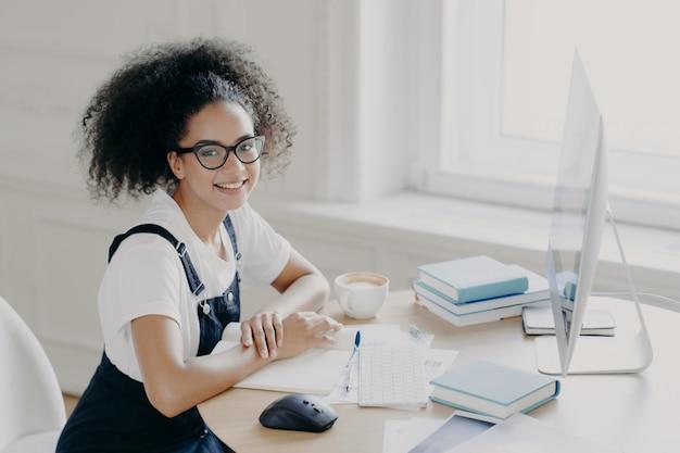 Pozytywna afroamerykańska freelancer pozuje w pracy z papierami i podręcznikami