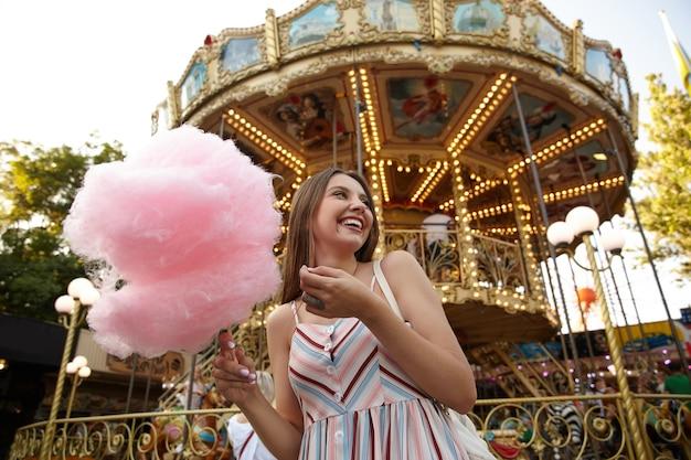 Pozytywna atrakcyjna kobieta z długimi brązowymi włosami ubrana w letnią sukienkę pozująca nad karuzelą w parku rozrywki w ciepły letni dzień, trzymająca watę cukrową na drewnianym patyku, patrząc na bok i uśmiechająca się radośnie