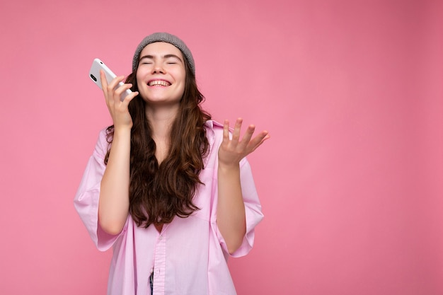 Pozytywna atrakcyjna młoda brunetka kobieta ubrana w stylową różową koszulę i szary kapelusz na białym tle na różowym tle, trzymając w ręku i za pomocą telefonu komórkowego do komunikacji i nagrywania wiadomości głosowej.