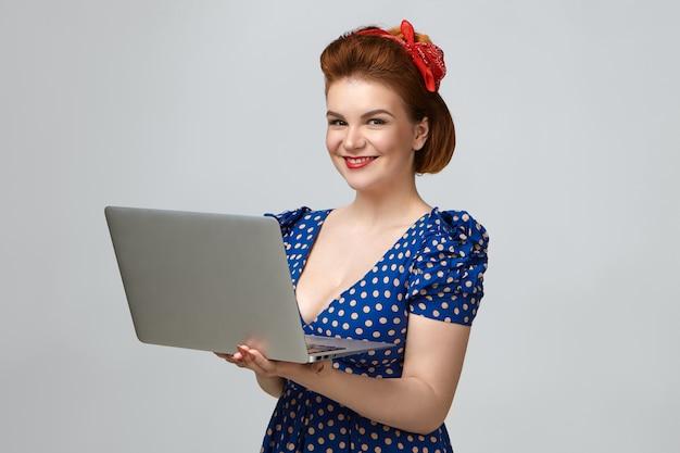 Pozytywna atrakcyjna młoda dama ubrana w sukienkę vintage i czerwoną szminkę pozowanie w studio, ciesząc się szybkim bezprzewodowym połączeniem internetowym za pomocą przenośnego komputera. ludzie