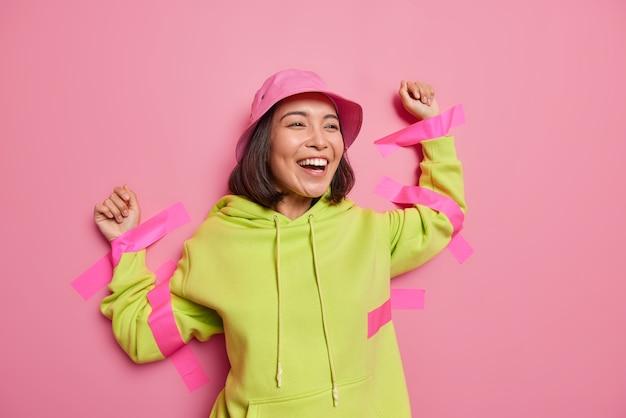 Pozytywna azjatka śmieje się radośnie przyklejona do ściany taśmami klejącymi, ubrana w panamę i bluzę z kapturem, która nie czuje się wolna odizolowana na różowej ścianie