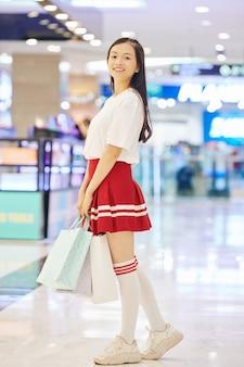 Pozytywna azjatycka uczennica trzymająca papierowe torby, gdy stoi w centrum handlowym