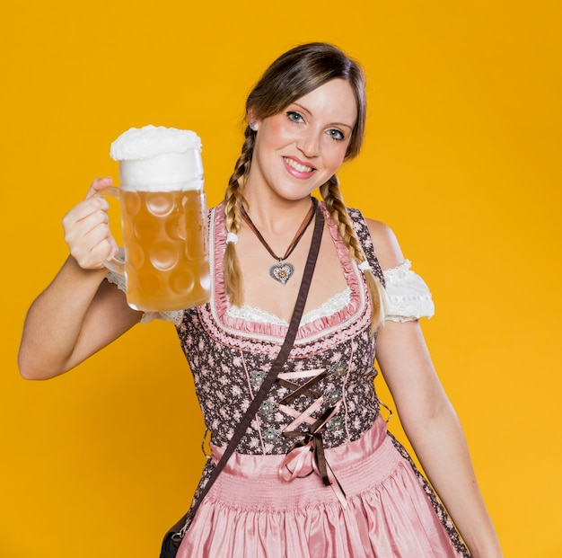 Pozytywna bawarska kobieta trzyma piwnego kubek