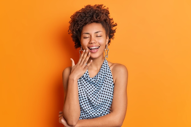 Pozytywna beztroska afroamerykanka śmieje się radośnie, trzymając zamknięte oczy