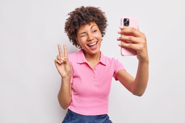 Pozytywna beztroska kobieta prowadzi rozmowę online przez smartfona sprawia, że gest pokoju mruga okiem szeroko uśmiechniętym portretem siebie ubranej swobodnie, odizolowanej na białej ścianie