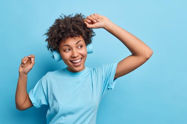 Pozytywna beztroska rozbawiona kędzierzawa nastolatka cieszy się życiem unosi ręce tańczy do ulubionej muzyki nosi bezprzewodowe słuchawki czuje się szczęśliwa na białym tle nad niebieską ścianą skopiuj miejsce na promocję