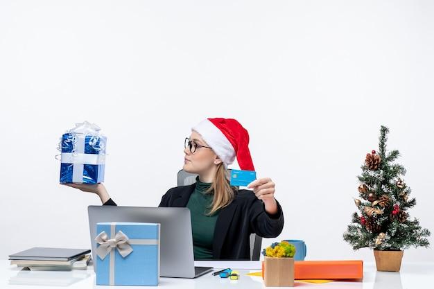 Pozytywna biznesowa kobieta w kapeluszu świętego mikołaja i okularach siedzi przy stole trzymając prezent na boże narodzenie i kartę bankową w biurze