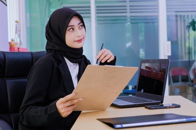 Pozytywna biznesowa młoda kobieta w biurze dostaje nowy pomysł