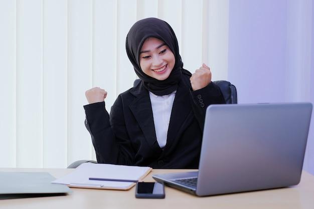 Pozytywna biznesowa młoda kobieta wesoła w biurze dostaje nowy pomysł