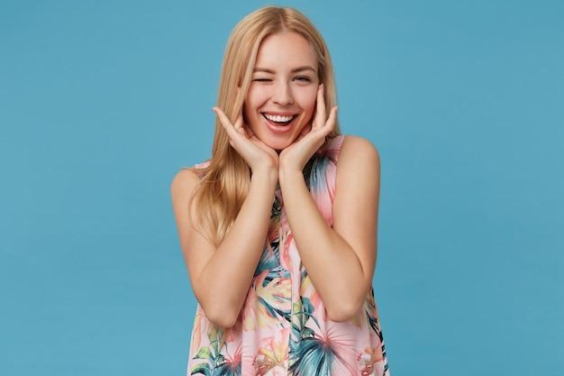 Pozytywna blond długowłosa dama ubrana w romantyczną sukienkę w kwiaty, stojąca z czarującym uśmiechem, mrugająca i opierająca głowę na uniesionych dłoniach
