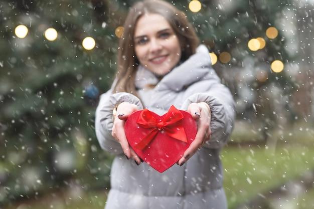 Pozytywna blond kobieta trzyma pudełko na ulicy podczas opadów śniegu. rozmycie tła