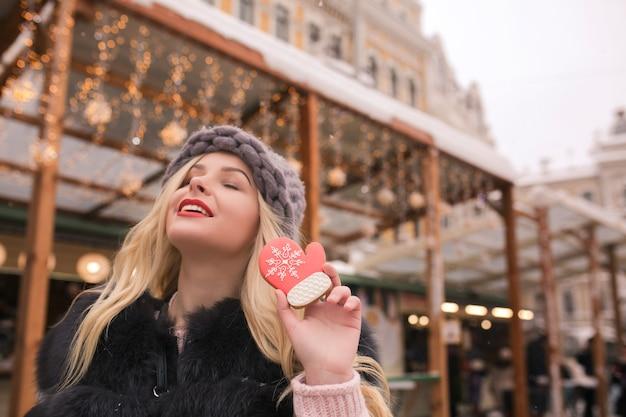 Pozytywna blond modelka z zamkniętymi oczami trzymająca smaczne piernikowe ciasteczko przy lekkiej dekoracji na placu w kijowie