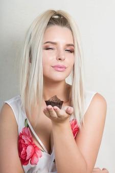 Pozytywna blondynka cieszy się słodką czekoladową babeczką