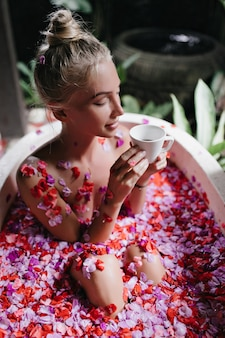 Pozytywna blondynka kobieta siedzi w skąpaniu z kwiatami i trzymając kubek. portret romantycznej opalonej kobiety picia herbaty podczas spa.