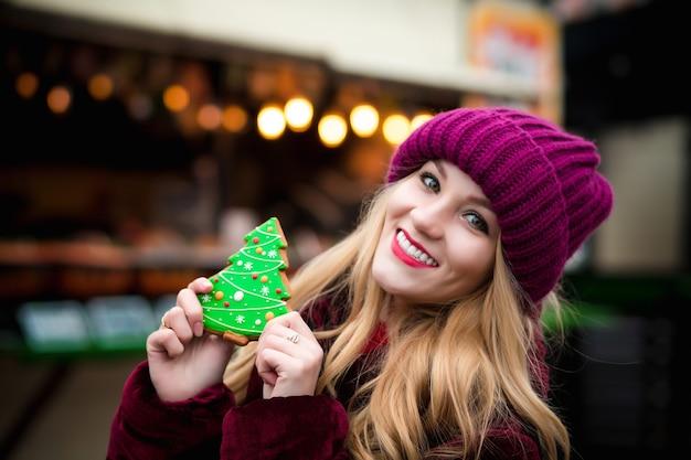 Pozytywna blondynka trzyma piernikowe ciastko, pozuje na jarmarku bożonarodzeniowym w kijowie