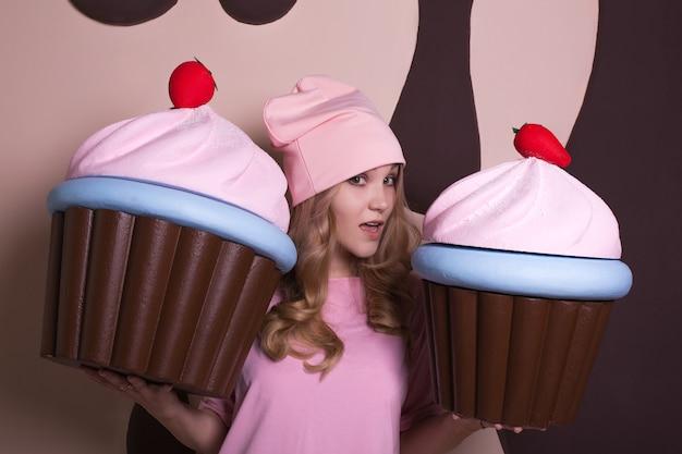 Pozytywna blondynka w różowej czapce, ciesząca się dużymi babeczkami w studio