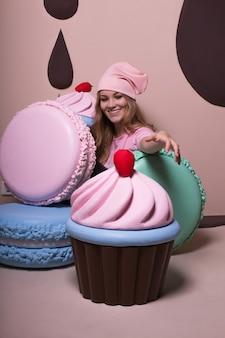 Pozytywna blondynka w różowej czapce i koszulce bawi się dużymi makaronikami i babeczkami w studio