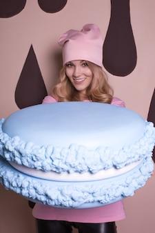 Pozytywna blondynka w różowej koszulce i czapce z dużym ciastem makaronikowym