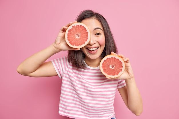 Pozytywna brunetka azjatka dobrze się bawi trzymając dwie połówki grejpfruta dostaje witaminy z owoców cytrusowych, uśmiecha się radośnie, ubrana w luźną koszulkę w paski na tle różowej ściany. witamina c