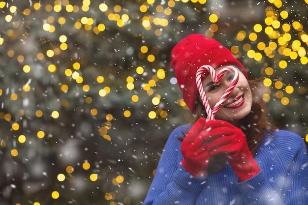 Pozytywna brunetka kobieta nosi czerwony kapelusz i niebieski sweter trzymając cukierki w pobliżu choinki podczas opadów śniegu. miejsce na tekst