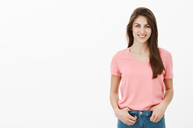 Pozytywna brunetka kobieta pozuje w studio