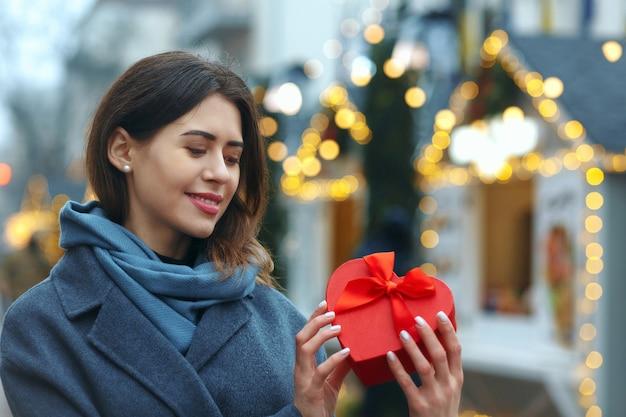Pozytywna brunetka kobieta trzyma pudełko w pobliżu choinki. miejsce na tekst
