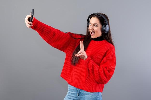 Pozytywna brunetka kobieta ubrana w czerwony sweter ze słuchawkami robi selfie ze smartfonem, odizolowana na szaro