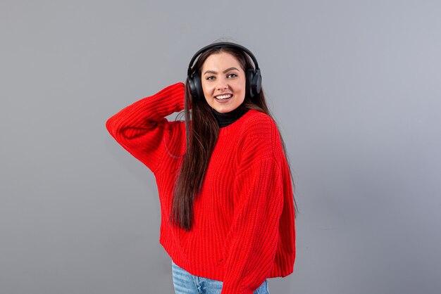 Pozytywna brunetka kobieta w czerwonym swetrze słucha muzyki na smartfonie w słuchawkach, na szarym tle